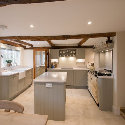 <p>A totally bespoke kitchen and boot room which shows how comfortable a new kitchen, designed in a traditional style, sits in a listed home. This beautiful Lay-On kitchen with walk-in pantry and bespoke sideboard has been painted in Farrow & Ball's Hardwicke White throughout and perfectly compliments the natural wooden beams and stonework.<br /> The Silestone Lagoon worktops and contemporary accessories bring the whole look up-to-date and provide the functionality (and luxury) that would have been missing when the house was built!<br /> Note how the exposed brickwork on the entrance to the Boot Room provides a unique framework – a feature of it's Grade II pedigree!<br /> The baskets, here, in the boot room were especially commissioned to fit the hand built unit. <br /> Other details; The kitchen tap is a Perrin & Rowe Oberon tap in polished chrome whilst the splendid walk-in pantry tap is a Zip HydroTap providing boiling, chilled and sparkling water. All handles are Brushed Nickel.</p>