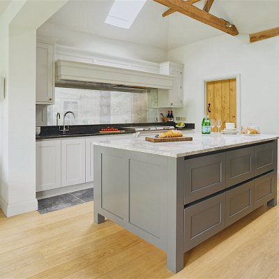 <p>We designed this handless Shaker kitchen for a beautiful family home in the stunning Bedfordshire countryside. The super-sized island is perfect for storage, food prep and eating. It's topped with Bianco Eclipsia Quartzite which is a natural product unlike the usual Quartz and the cabinets are painted in Farrow & Ball's Downpipe. The sink run, wall units and large mantel have been cleverly colour matched to the Everhot Range Cooker. For a complimentary look-and-feel to the island, the worktop here is a naturally textured Steel Grey Satinato Granite. A real touch of glam has been added with the impressive mirrored splashback in a Hand Silvered Vintage Finish!</p>